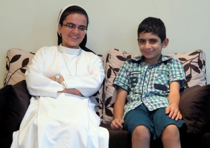 Sister Angela and Bhnam (last name withheld for privacy reasons) from St. Anne's Orphanage in Alqosh, Iraq, relax on a couch at the Daughters of Mary covenant inAnkawa, Iraq. On Aug. 6, 2014, six children and staff remaining in the orphanage fled fromAlqoshin front of advancing forces of the group calling itself Islamic State. Normally a two hour trip, it took seven hours of hot, dusty checkpoints and clogged roads. St. Anne's Orphanage is supported by MCC.