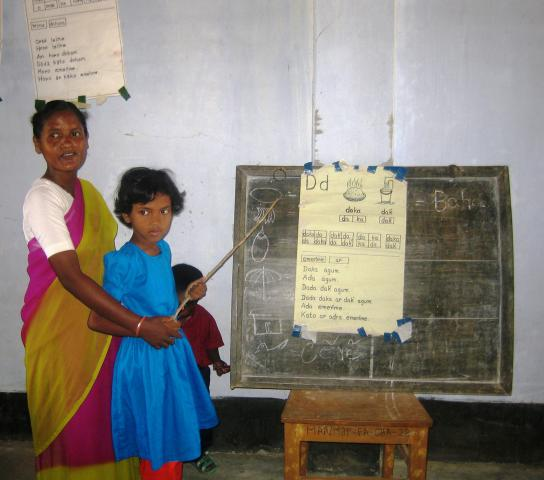In Bangladesh, preschool teacher Costantina Mandri helps Moumita Tudu with a literacy activity. Although Bengali is the national language in Bangladesh, there are some 45 different indigenous language groups. More than half of children from these groups drop out of primary school, often because of language barriers. MCC supports preschools that begin instruction in children's own languages and gradually introduce Bengali over a two-year period.
