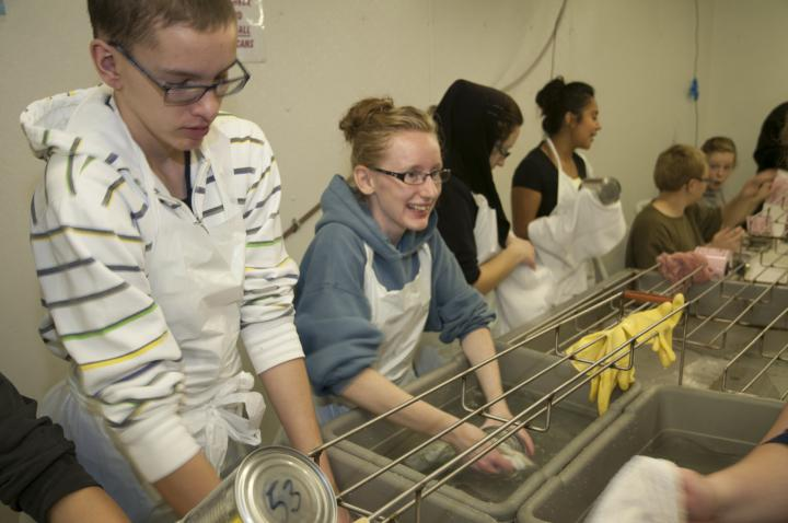 Step 7: The freshly cooked and cooled cans are individually hand-washed and dried off by volunteers.