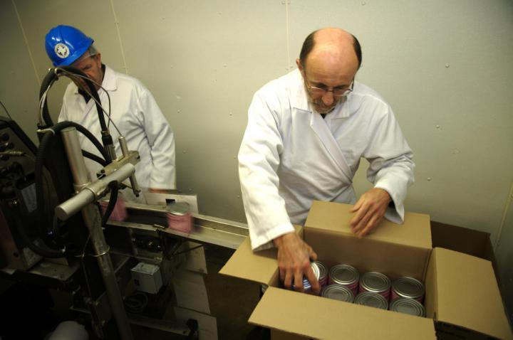 Step 9: The labeled cans go through a printer which applies the production and expiration dates, before they are placed in boxes with 24 cans in each one.