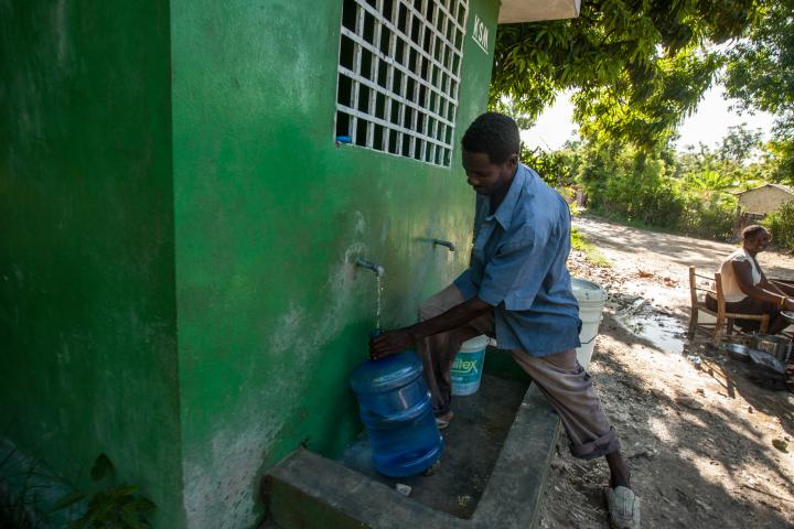 Germain Isaac fills a jug with clean water in Desarmes, a rural town in the Artibonite Valley, the center of Haiti's cholera outbreak. In response to the threat of cholera, MCC built 32 kiosks and 11 fountains, drawing water from springs in the mountains to town. A local water committee manages each kiosk or fountain. Families using the water pay a small monthly fee, which the committee can use for repairs.