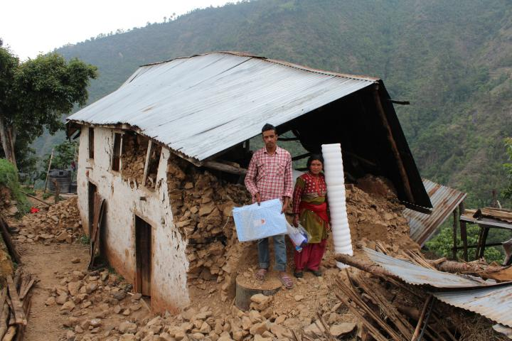 Hari Ghimire and his wife Nirmala hold the tarp and sleeping mats they received from MCC, through RIOCD.
