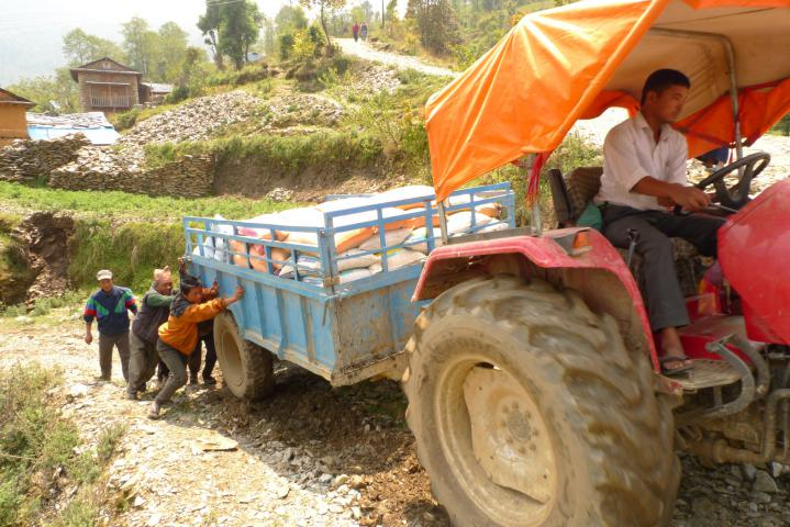 Pushing a tractor full of relief supplies up a gravelly hill. These supplies are part of MCC's relief response in the Okhaldhunga District. Through our local partner Group of Helping Hands (SAHAS) families will receive enough food to last a household of five, for three weeks. They will also receive emergency shelter materials, blankets and cooking supplies, flashlights, water treatment supplies and soap​​.