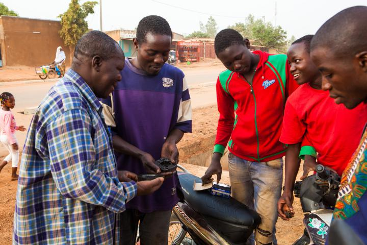 Papou Sana, center,is a participant in MCC's restorative justice partner Lieux de Vie, which supports current and formerly imprisoned youth through social programs and apprenticeships.Sana is learning mechanical skills frommechanic Claude Ouédraogo, in purple. (Papou Sana's real name is not used to protect his privacy.)
