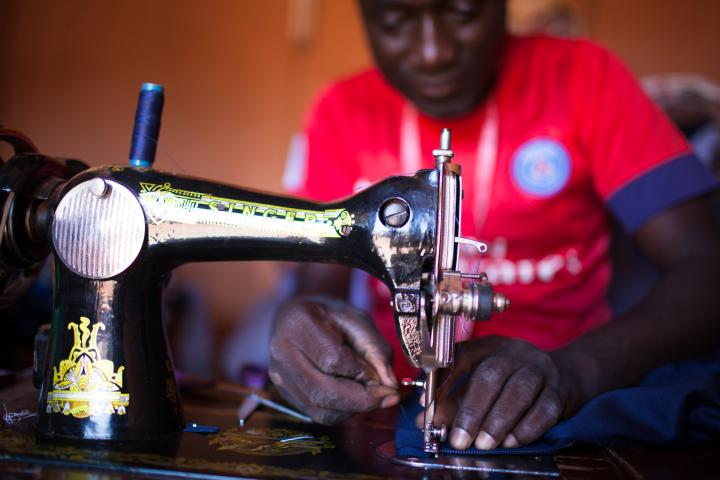 Zacharia Sawadogo, a tailor in Ouagadougou, Burkina Faso, teaches young men how to sew and alter men's clothingwhile serving out their prison time at MCC partner Lieux de Vie.