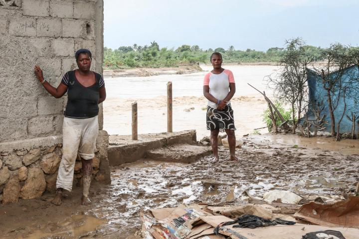 Haitian women stand where their houses used to be.