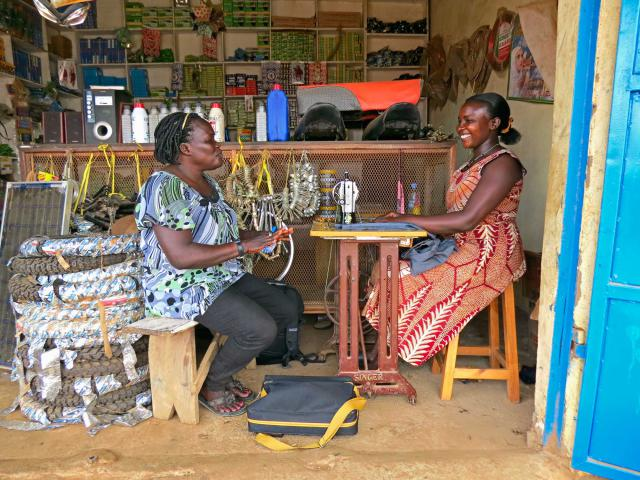 Two women sit in a motorcycle shop, one at a sewing machine