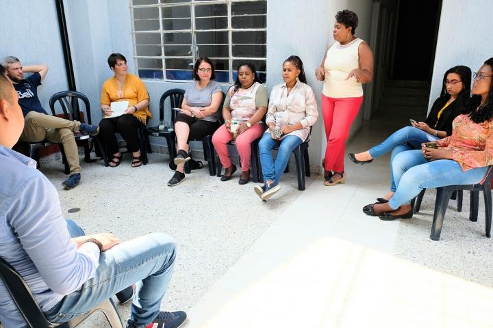 Woman speaks to group sitting in a circle.