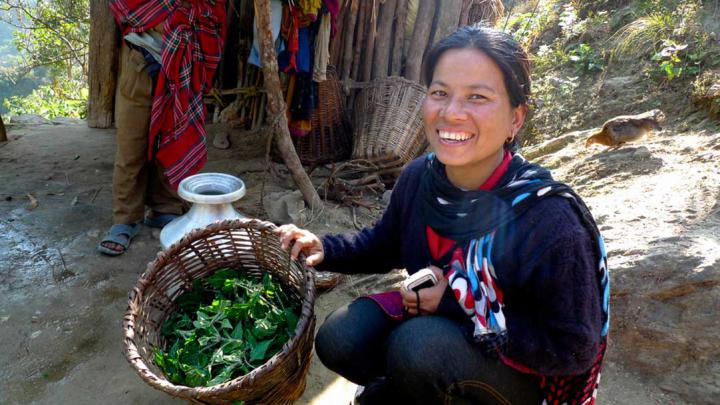Smiling women squats next to a basket filled with leaves
