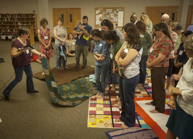 "Sue Eagle, left, a coordinator of Indigenous Work for MCC Canada, pulls away a blanket, symbolizing the loss of Indigenous land and rights, during an exercise called ""The Loss of Turtle Island."" The group exercise in Newton, Kan., was hosted by MCC Central States to strengthen awareness of Indigenous issues in the region."