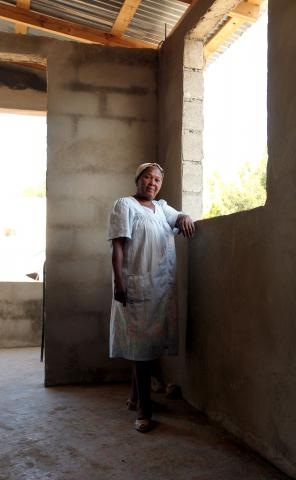 Elumene Charles stands in her newly repaired home made possible by MCC partner ACCESS with funding from MCC's earthquake response effort.  The $180,000 project allowed ACCESS to repair 45 homes and build five new latrines in the Boulard neighborhood of Port-au-Prince. At least five people live in each home.