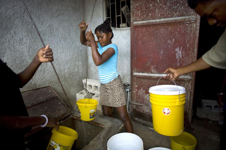 Volunteers Evening Louis, left, and Sainterne Beona, right, draw water from a cistern at an MCC-supported water distribution site in Cité Soleil, part of Port-au-Prince. MCC's priority on emergency assistance, like this, is gradually refocusing on self-sustaining priorities.