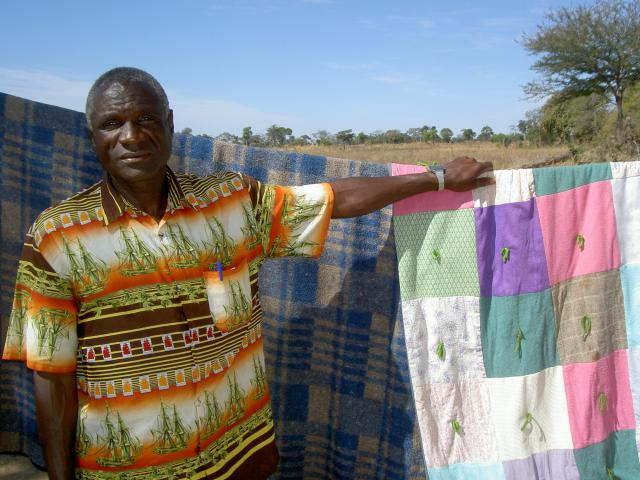 Leonard Sintumbi stands beside an MCC blanket that Compassionate Care's home-based care workers gave him when he was very sick with HIV.