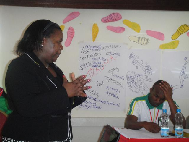 Doreen Ruto, director of Daima Initiatives for Peace and Development, leads a retreat for first responders, including participant Charles Mugo, on trauma healing after the attack on the Westgate mall in Nairobi, Kenya.(MCC Photo/Katie Mansfield)