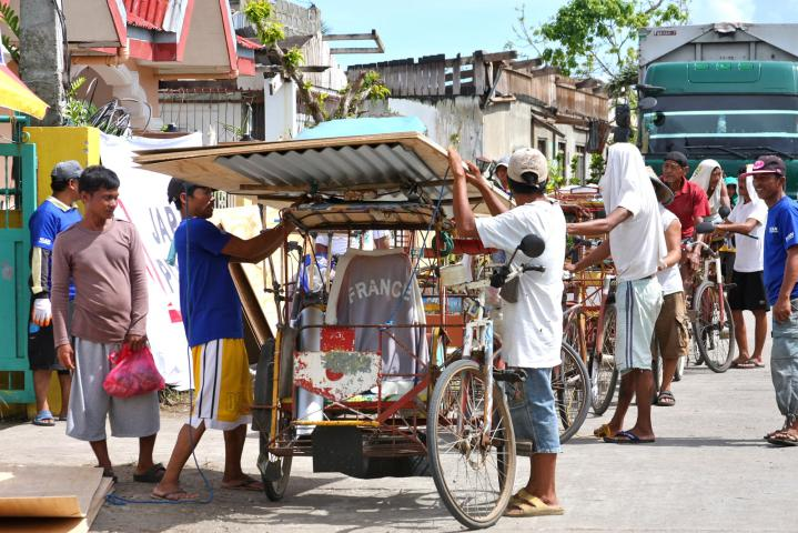 MCC is supplying building materials, including plywood and tin sheets similar to those being loaded onto this bicycle-powered rickshaw, to almost 3,000 Filipino families whose homes were destroyed by Typhoon Haiyan. In addition, MCC is paying local people to build the houses in the towns of Naval and Dulag. (MCC Photo/Laura Armstrong)