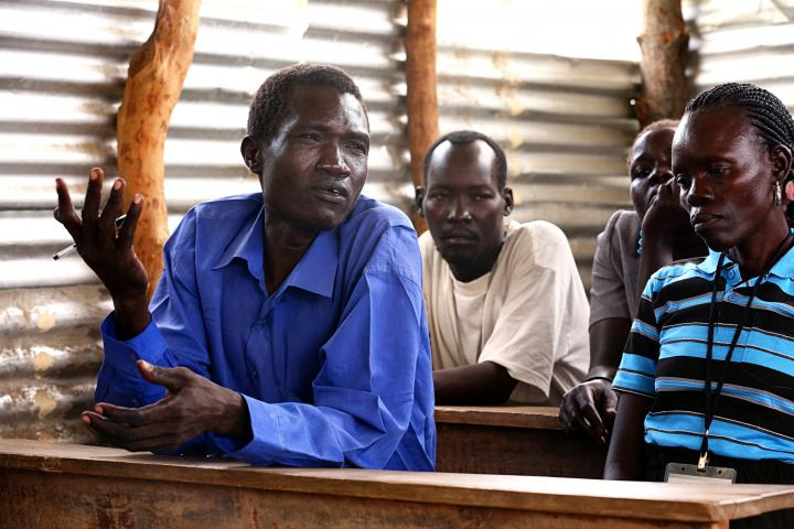 Caesaer Hakim (left) and other members Michael Lagu, Agnew Masudio and Cecilia Eppe attend an Opari peace committee meeting held in a school classroom.