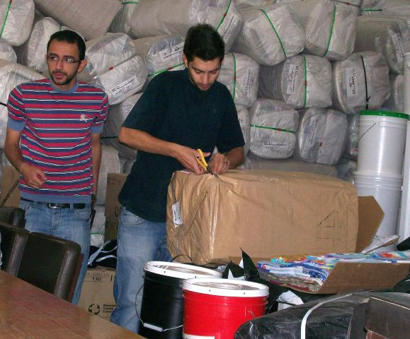 Basil Kaboushi, left, and Wajdi Haddad, volunteers with Caritas Jordan, an MCC partner, help to distribute MCC relief kits and comforters to Syrian refugees at the Latin Patriarchate School in Mafraq, Jordan, in June.