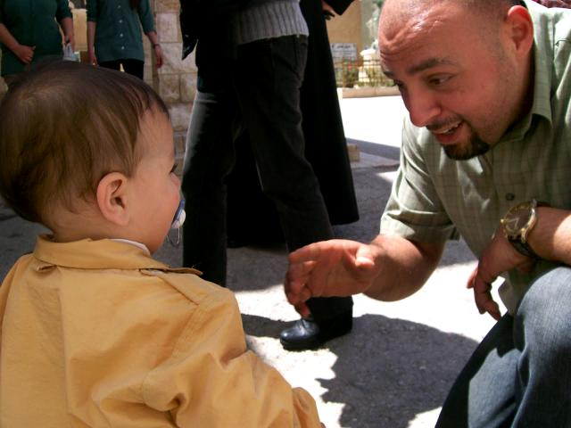 Jameel Dababneh, Caritas Jordan's emergency response coordinator, welcomes a young Syrian refugee. MCC partners with Caritas Jordan, one of the organizations that welcomes refugees, offers material resources and links them to services.