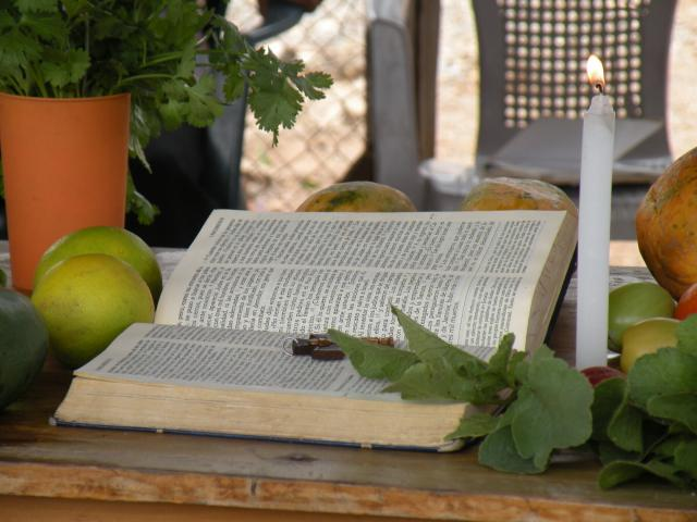 an open bible lies on a table next to fruit and a candle