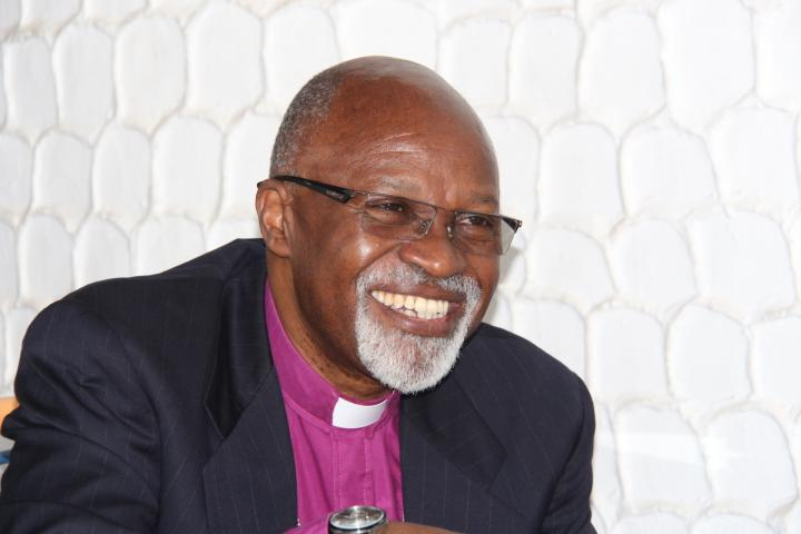 A man wearing a suit and bishop's collar smiles and looks to the side