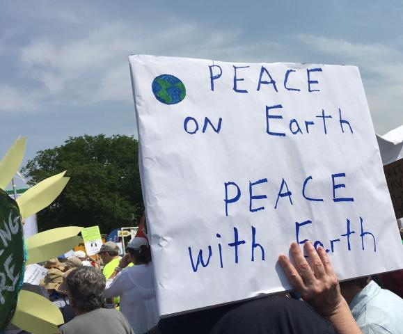 "Person holds a protest sign reading ""Peace on Earth Peace with Earth"""