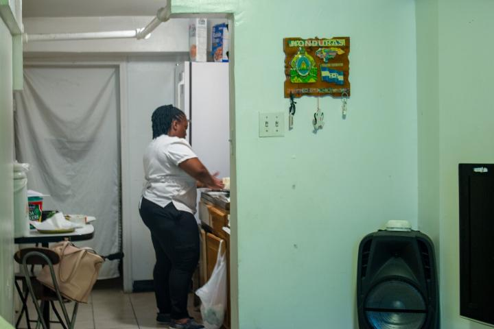 A woman stands in a kitchen preparing corn tortillas