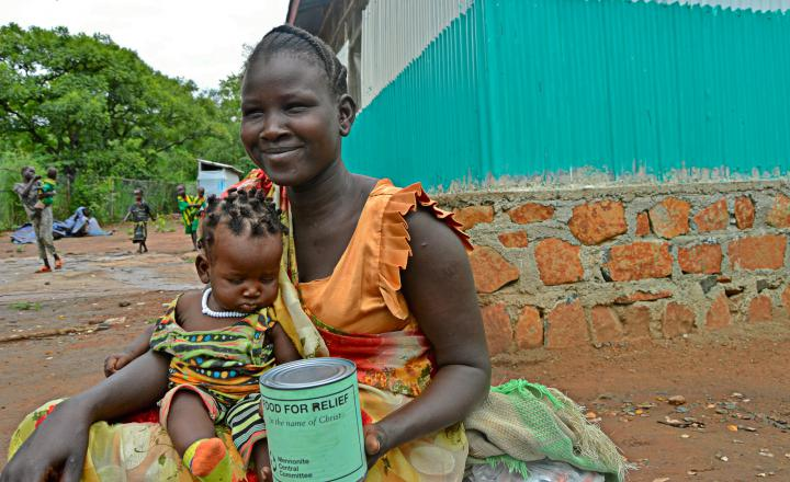 A smiling women holds a baby in her lap and a can of meat.