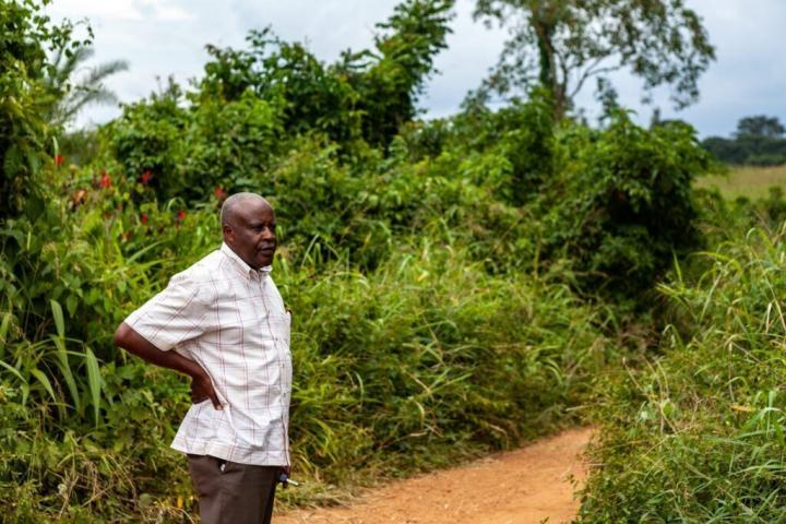 A black man wearing a white short-sleeved button up shirt stands in the middle of a red dirt road, surrounded by greenery. He has one hand on his hip and looks off to the right.