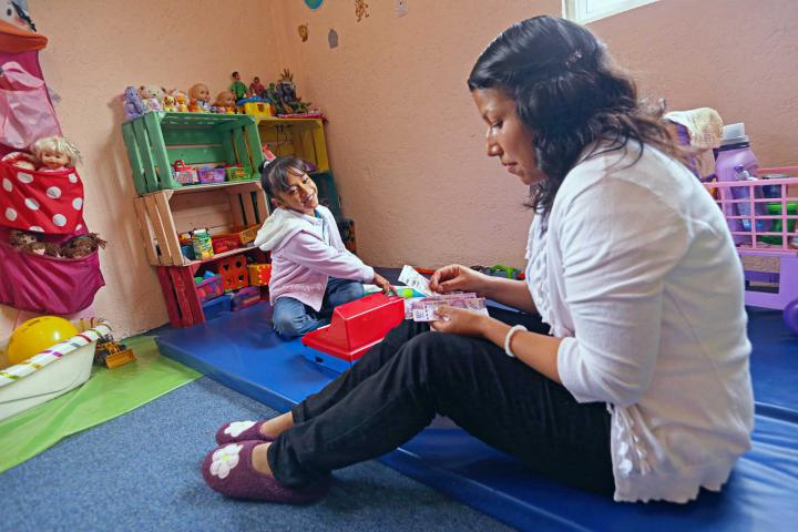 A smiling young girl sits on a play matt with a teacher.