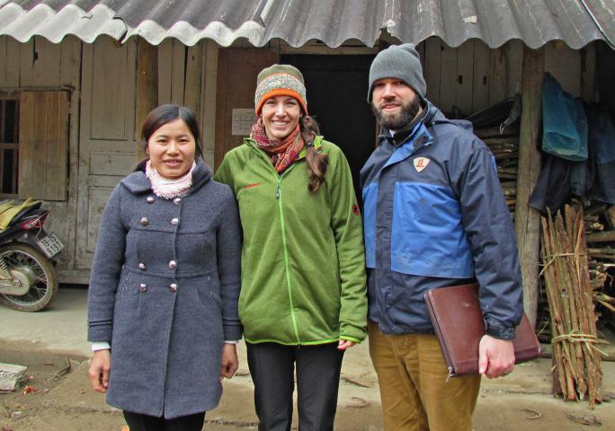 The Treadways and Phung Thi Gia wearing jackets and scarves stand in front of a building.