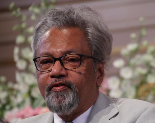 Close up of a man with silver hair and a beard wearing glasses and a gray suit jacket.